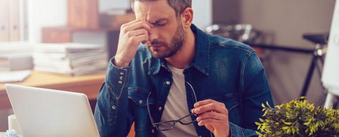 man with headache at desk