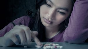 female looking at pills on a table