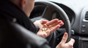 person holding pills in car